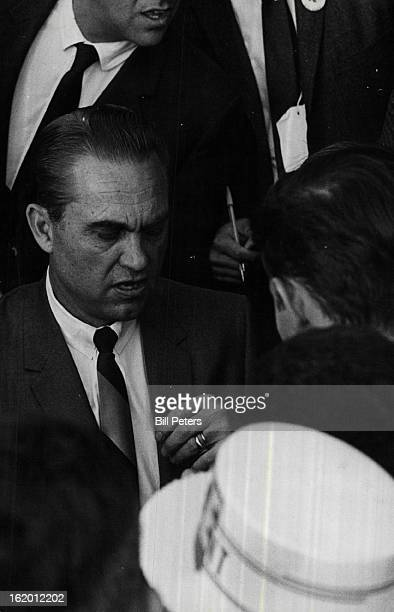 OCT 11 1968 OCT 12 1968 Wallace surrounded by newsmen held brief impromptu press conference after speech during which he had to shout over crowd's...