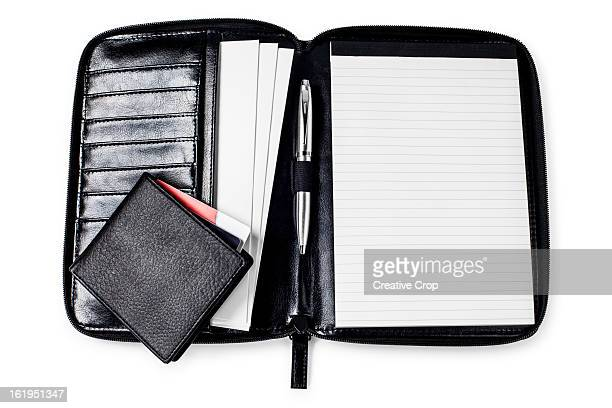 Wallet, credit card and pen, on a blank day book