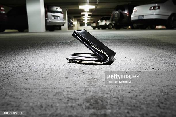 Wallet on concrete in parking garage (focus on wallet)