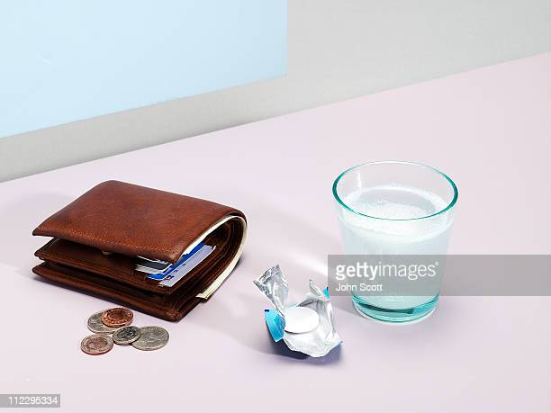 Wallet with headache tablet and glass of water