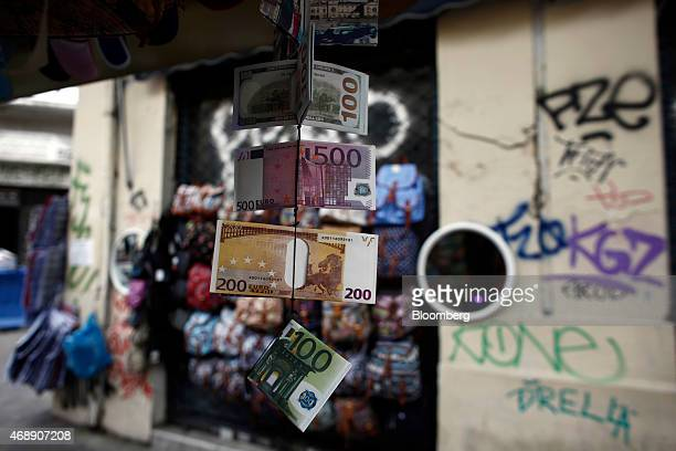 Wallets decorated with euro and US dollar banknote designs hang from a street vendor's store in Athens Greece on Wednesday April 8 2015 Russian...