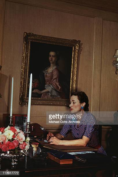 Wallis Duchess of Windsor sitting at a desk a portrait hangs on the wall behind her in Goverment House in Nassau the Bahamas circa 1942 The Duke of...