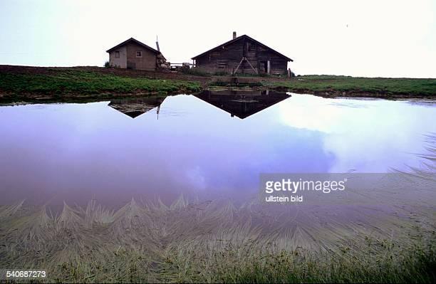 Wallis RiederalpWallis Schweiz Almhütten spiegeln sich in einem Bergsee bei Riederalp
