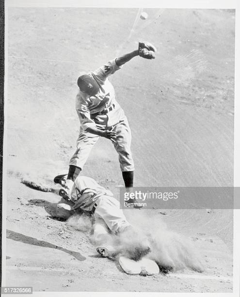 Wally Moses right fielder for the Philadelphia Athletics slides safely into third on Newsome's infield hit as first sacker Kuhel throws over...