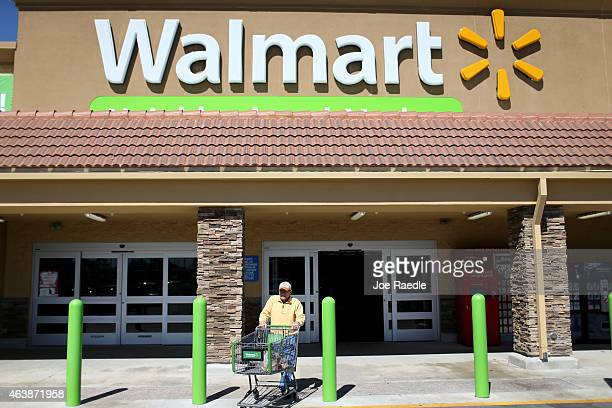 Walmart customer exits from the store on February 19 2015 in Miami Florida The Walmart company announced Thursday that it will raise the wages of its...