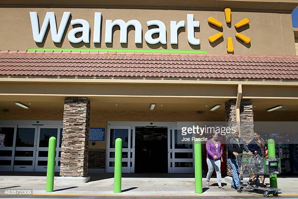 Walmart customers exit from the store on February 19 2015 in Miami Florida The Walmart company announced Thursday that it will raise the wages of its...