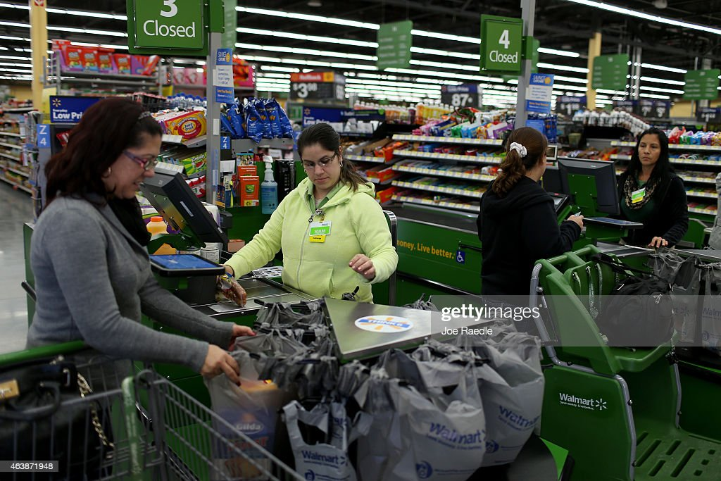 Walmart employee Adriana Cajuso rings up the purchases of customer Yoalmi Matias as she checksout at a Walmart store on February 19 2015 in Miami...