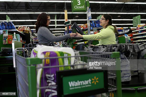 Walmart employee Adriana Cajuso takes payment from customer Yoalmi Matias as she checksout at a Walmart store on February 19 2015 in Miami Florida...