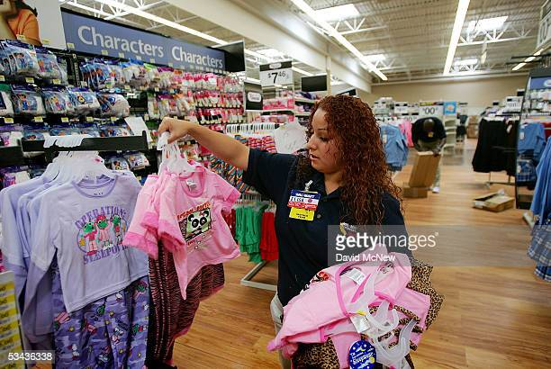 WalMart employee Alisa Luna stocks merchandise at the soontobeopened WalMart Palmdale Supercenter department store on August 18 2005 in Palmdale...