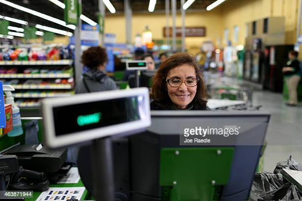 Walmart employee Blanca Mojita rings up a customers purchases at a Walmart store on February 19 2015 in Miami Florida The Walmart company announced...