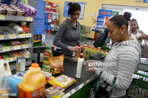 Walmart employee Darlin Cienfuegos rings up customer purchases at a Walmart store on February 19 2015 in Miami Florida The Walmart company announced...
