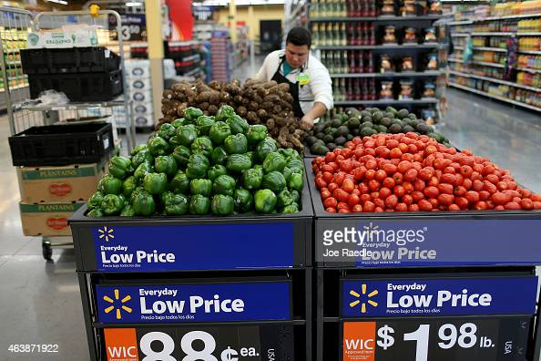 Walmart employee Dayngel Fernandez works in the produce department stocking shelves at a Walmart store on February 19 2015 in Miami Florida The...