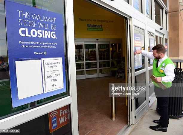 Walmart employee hangs signs on the front entrance telling customers that this store location will be closing in two days Walmart has announced...