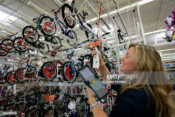 WalMart employee Sandy Johnson stocks merchandise at the soontobeopened WalMart Palmdale Supercenter department store on August 18 2005 in Palmdale...