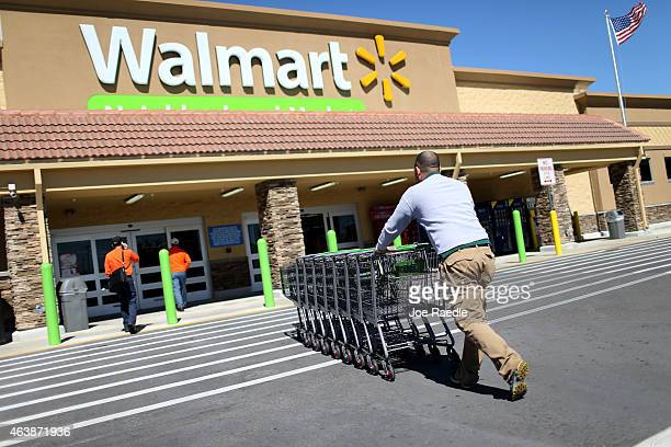 Walmart employee Yurdin Velazquez pushes grocery carts at a Walmart store on February 19 2015 in Miami Florida The Walmart company announced Thursday...