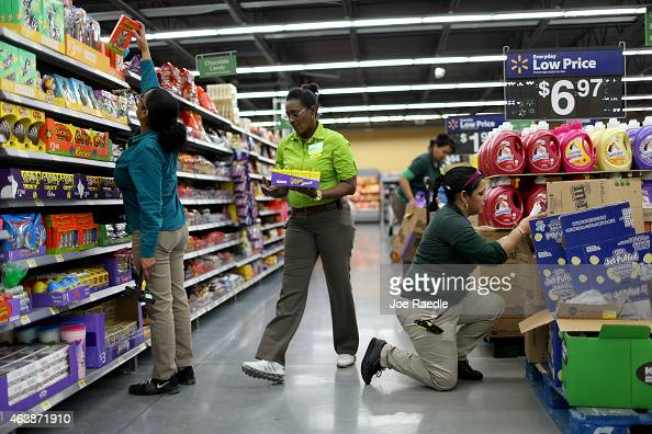 Walmart employees Iliana Sanchez and her fellow employees stock the shelves at a Walmart store on February 19 2015 in Miami Florida The Walmart...