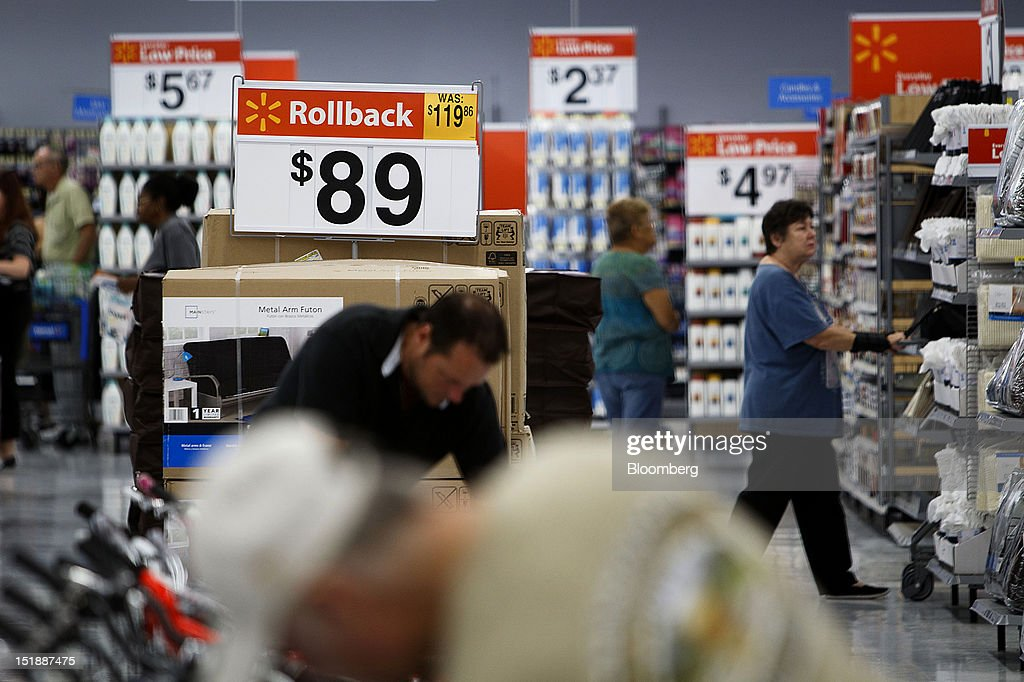 Wal-Mart Rollback pricing signs are displayed while customers shop during the grand opening of a new Wal-Mart Stores Inc. location in Torrance, California, U.S., on Wednesday, Sept. 12, 2012. The Wal-Mart store, which was the first location to open in Los Angeles County since 2006, was built inside of a former Mervyn's clothing location. Photographer: Patrick Fallon/Bloomberg via Getty Images