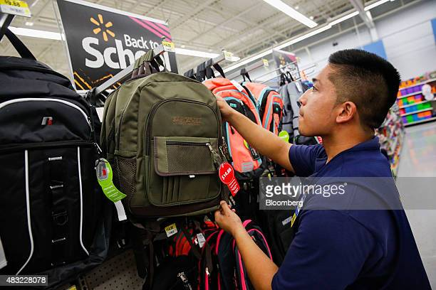A WalMart Stores Inc associate stocks backpacks at a WalMart Stores Inc location in the Porter Ranch neighborhood of Los Angeles California US on...