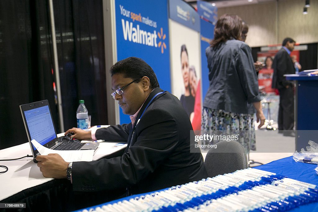 Wal-Mart Stores Inc. job recruiter Jayesh Hirani enters job seekers' resume information into a computer at the Black Data Processing Associates (BDPA) career fair in Washington, D.C., U.S., on Friday, Aug. 16, 2013. The U.S. Department of Labor is scheduled to release initial jobless claims on Aug. 22. Photographer: Andrew Harrer/Bloomberg via Getty Images