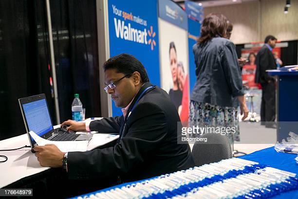 WalMart Stores Inc job recruiter Jayesh Hirani enters job seekers' resume information into a computer at the Black Data Processing Associates career...