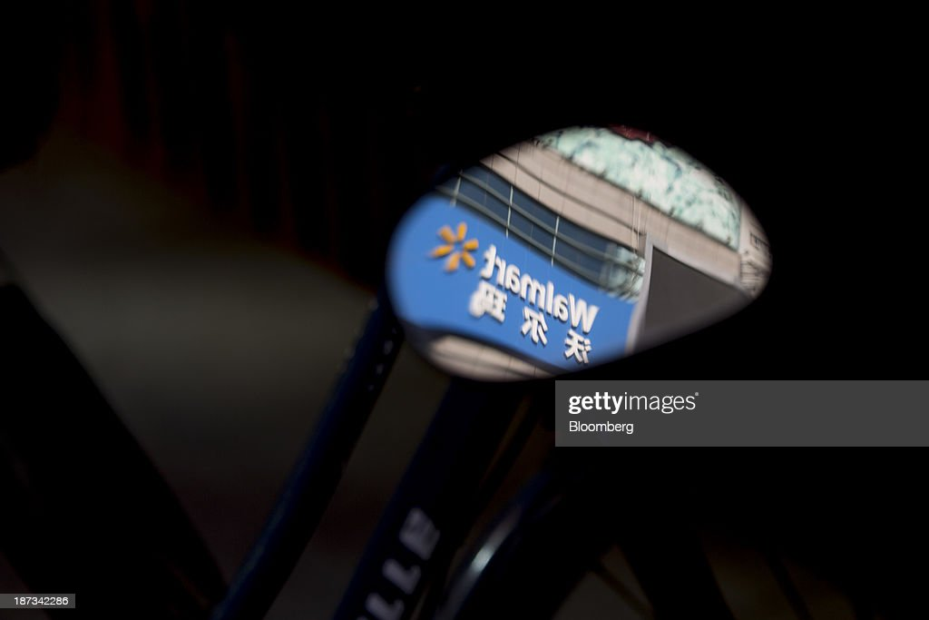A Wal-Mart Stores Inc. outlet logo is reflected on a mirror in Jinan, China, on Thursday, Nov. 7, 2013. The third plenary session of the 18th Communist Party of China Central Committee will be held from Nov. 9 to Nov. 12 in Beijing. Photographer: Brent Lewin/Bloomberg via Getty Images