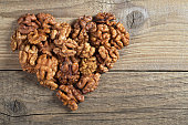 Walnut kernels in shape of heart on old wooden background, top view with space for text. The concept of a healthy eating