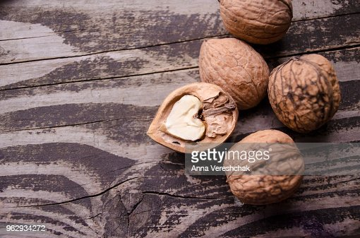 Walnuts on a grey textured wooden table. Assortment of nuts isolated on rustic old wooden background and splintered walnut with heart-shaped core. Walnuts close up : Stock Photo