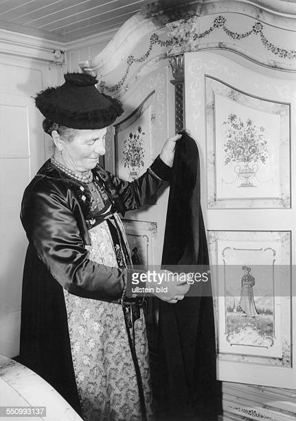 Walsertal regional costumes women in garb old peasant woman wearing the so called Walser garbm standing infront of a hand decorated wardrobe