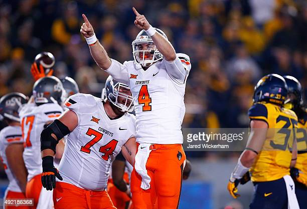 W Walsh of the Oklahoma State Cowboys celebrates after throwing a pass for a touchdown in the third quarter against the West Virginia Mountaineers...