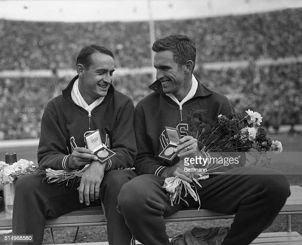 Walt Davis and Lt Ken Wiesner flash victory smiles and Olympic medals at Helsinki after they placed first and second respectively in the High Jump...