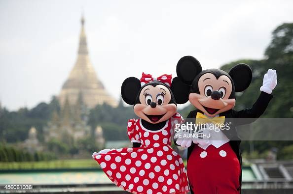 Walt Disney characters Mickey Mouse and Minnie Mouse pose for photographs in front of the Shwedagon Pagoda in Yangon on September 25 2014 The Disney...