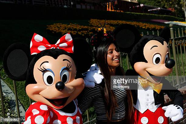 Walt Disney Co characters Minnie Mouse and Mickey Mouse take pictures with a guest at Disneyland Park part of the Disneyland Resort in Anaheim...