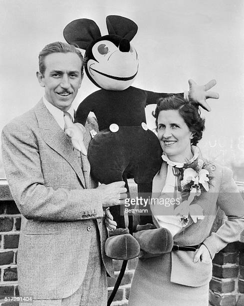 Walt Disney creator of the worldfamous Mickey Mouse is pictured with Mrs Disneywho helped him invent his famous cartoon characteras they arrived at...