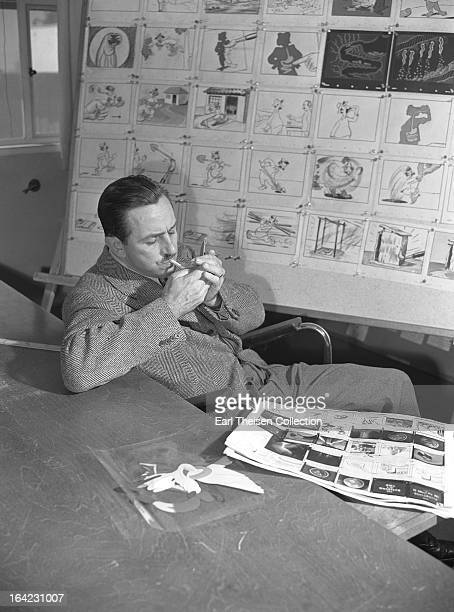 Walt Disney lights a cigarette while seated next to a storyboard for the commisioned animated short 'Hookworm' circa 1945 in Los Angeles California