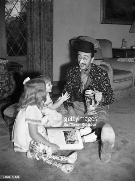 Walt Disney poses for a portrait at home with daughters Diane and Sharon circa 1938 in Los Angeles California