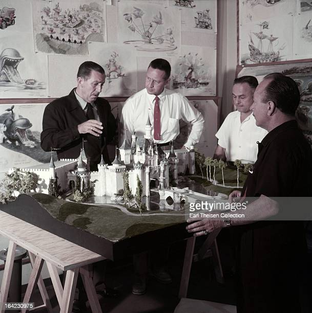 Walt Disney stands by a plan and model of Disneyland and chats with some imagineers circa 1954 in Los Angeles California
