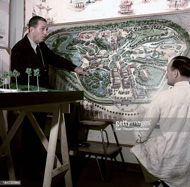 Walt Disney stands by a plan of Disneyland and chats with an imagineer circa 1954 in Los Angeles California