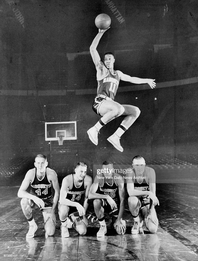 Walt Mangham of Marquette University jumps over teammates Do