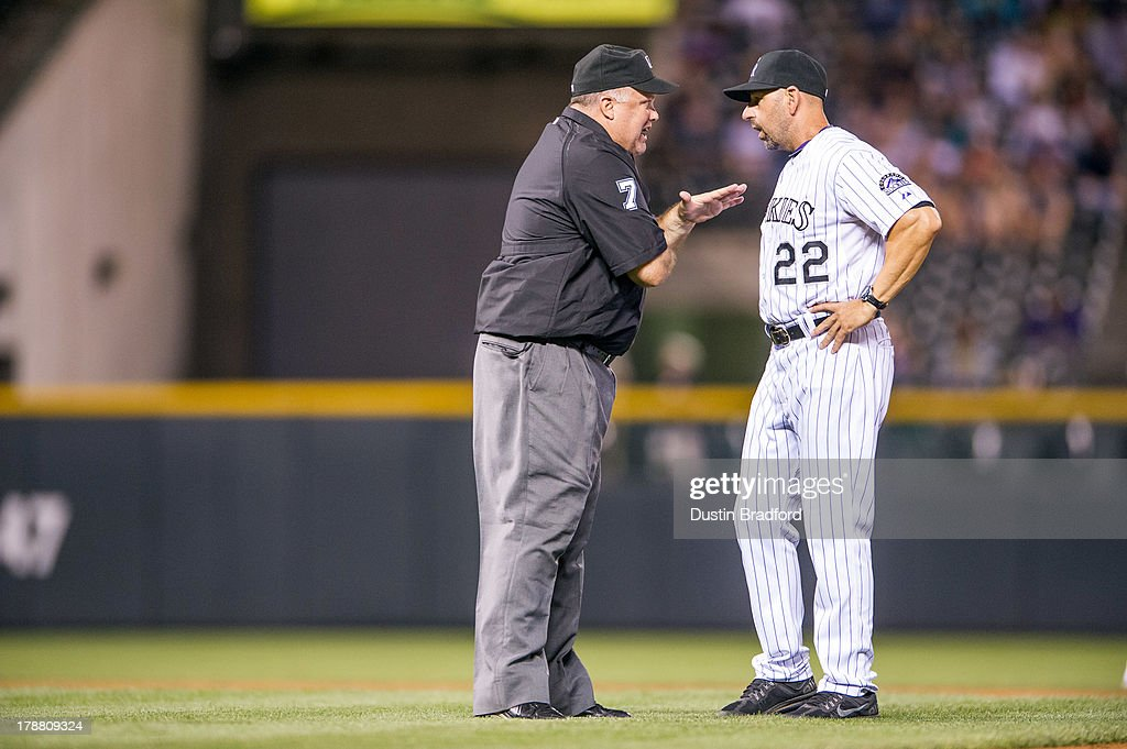 Walt Weiss #22 of the Colorado Rockies discusses a call with umpire Brian O'Nora #7 during the ninth inning of a game between the Colorado Rockies and the Cincinnati Reds at Coors Field on August 30, 2013 in Denver, Colorado. The Rockies beat the Reds 9-6.