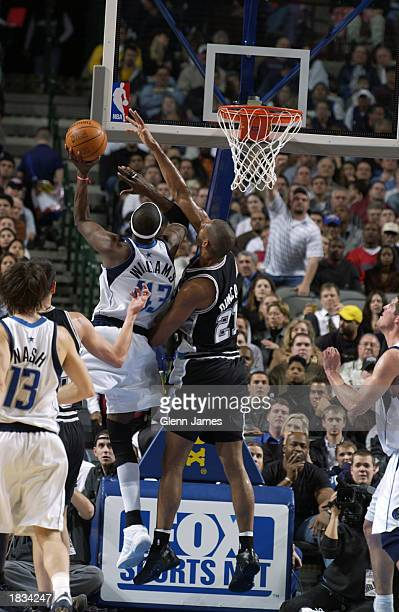 Walt Williams of the Dallas Mavericks drives to the basket against Tim Duncan of the San Antonio Spurs defends during the NBA game at the American...