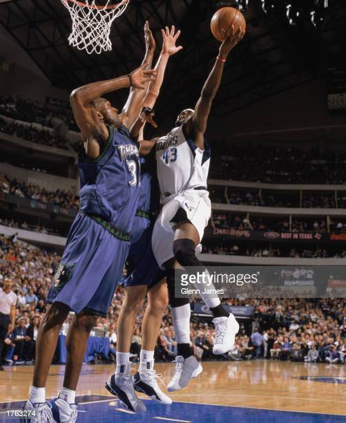 Walt Williams of the Dallas Mavericks goes for a basket over Joe Smith of the Minnesota Timberwolves during the NBA game at American Airlines Center...
