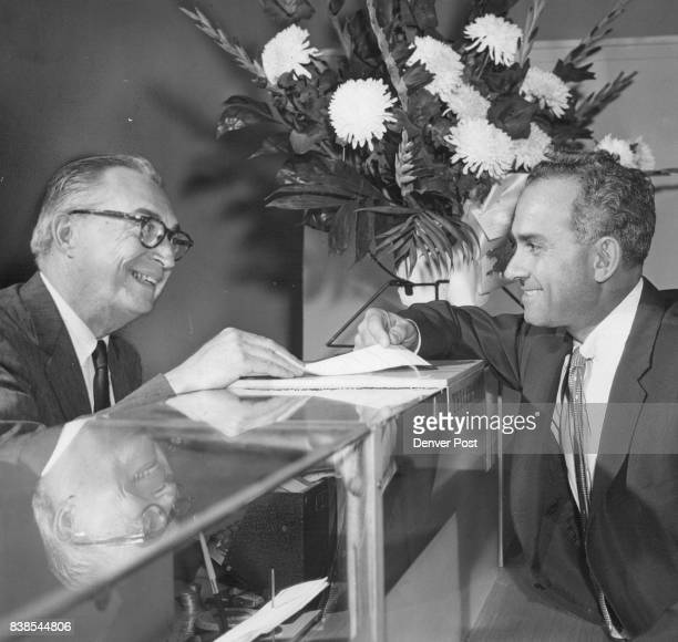 Walter A Woods president of the new Guaranty Bank Trust Co greets his first customer Louis W Nasbarg in the bank's temporary quarters at 1725...