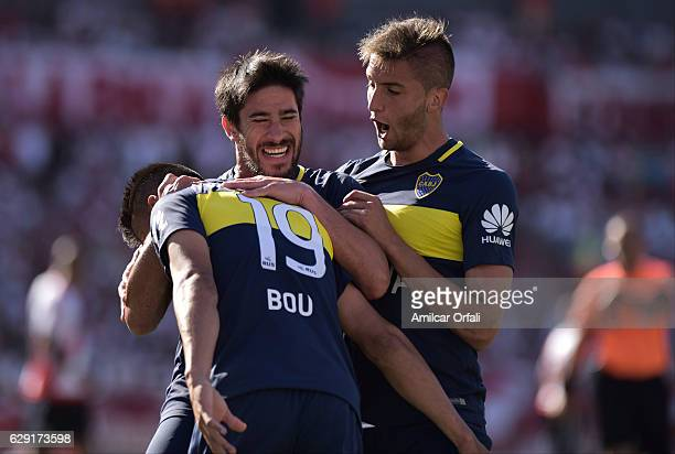Walter Bou of Boca Juniors celebrates with teammates Pablo Perez and Rodrigo Bentancur after scoring the first goal of his team during a match...