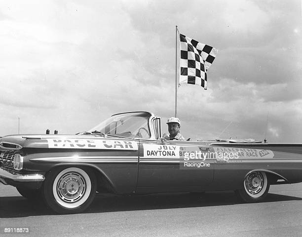 Walter Cronkite at the wheel of the pace car for the 1959 Firecracker 250 at Daytona Bill France Sr is in the passenger seat