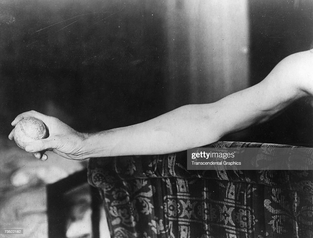 Walter Johnson star pitcher of the Washington Senators shows off his famous arm in a photo session in 1924