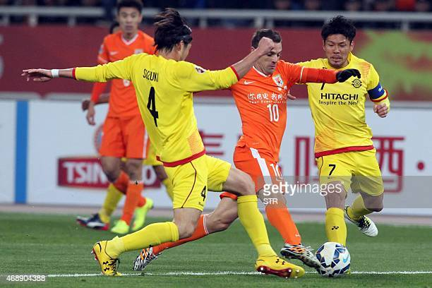 Walter Montillo of China's Shandong Luneng FC tussles for the ball with Daisuke Suzuki and Otani Hidekazu of Japan's Kashiwa Reysol during their AFC...