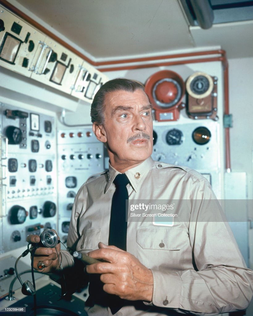 Walter Pidgeon (1897-1984), Canadian actor, wearing a beige shirt and black tie, standing in front of a control consolde with a microphone in his hand, in a publicity still issued for the film, 'Voyage to the Bottom of the Sea', 1961. The science fiction film, directed by Irwin Allen (1916-1991), starred Pidgeon as 'Admiral Harriman Nelson'.