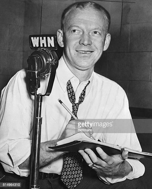 Walter 'Red' Barber sportscaster is shown writing as he is seated behind a microphone