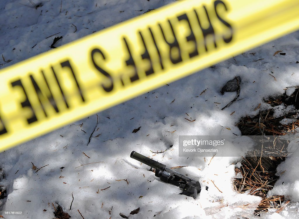 Walter Suppressor hand gun sits in the snow just off Glass Road near where former Los Angeles Police Department officer crashed the purple Nissan truck before carjacking a second truck as he was fleeing form law enforcement on February 15, 2013 in Big Bear, California. The gun was spotted February 15, by a local citizen. Dorner barricaded himself in a cabin near Big Bear, California, and engaged law enforcement officers in shootout, shooting two police, killing one and wounding the other. Dorner, a former Los Angeles Police Department officer and Navy Reserve veteran, who's body was identified in the burned cabin, was wanted in connection with the deaths of an Irvine couple and a Riverside police officer.