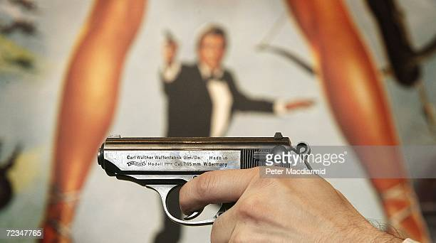 Walther PPK handgun is held up infront of a poster of the film 'For Your Eyes Only' during promotion of a sale of weapons from James Bond films on...